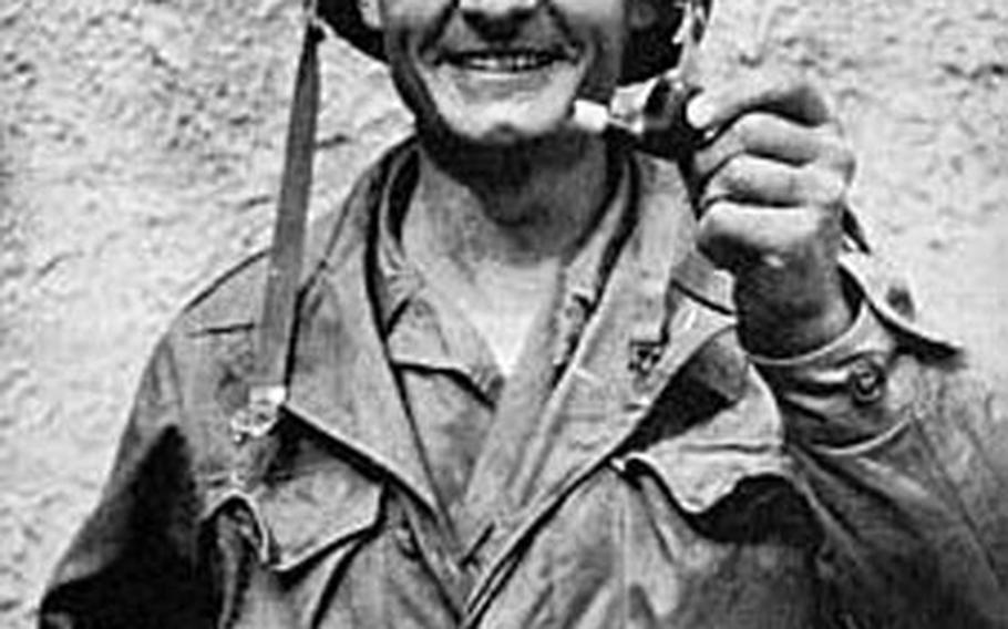 Father Emil Kapaun shows his pipe, which was shot out of his mouth by a sniper during the Korean War.