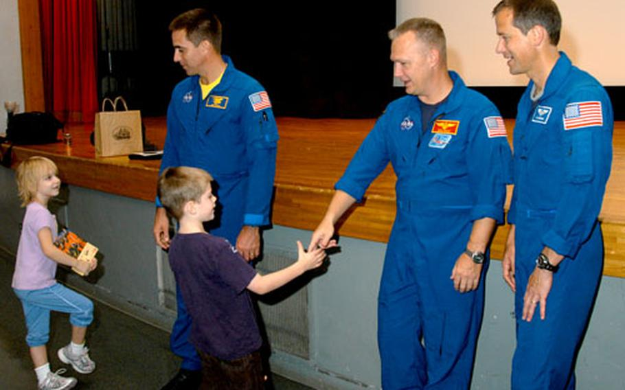From left, astronauts Cmdr. Chris Cassidy, Col. Doug Hurley and Dr. Thomas Marshburn greet Yokosuka Naval Base residents at the Benny Decker Theater on Wednesday. Earlier, the astronauts spoke to base students about their adventures.