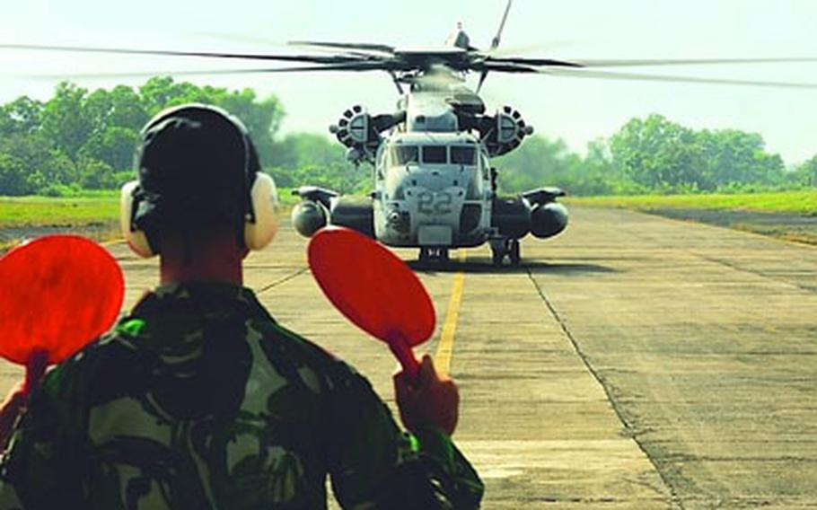 A member of the Indonesian military directs a U.S. CH-53E Super Stallion helicopter across the runway at Tabing Airfield in Padang, Indonesia, on Tuesday.