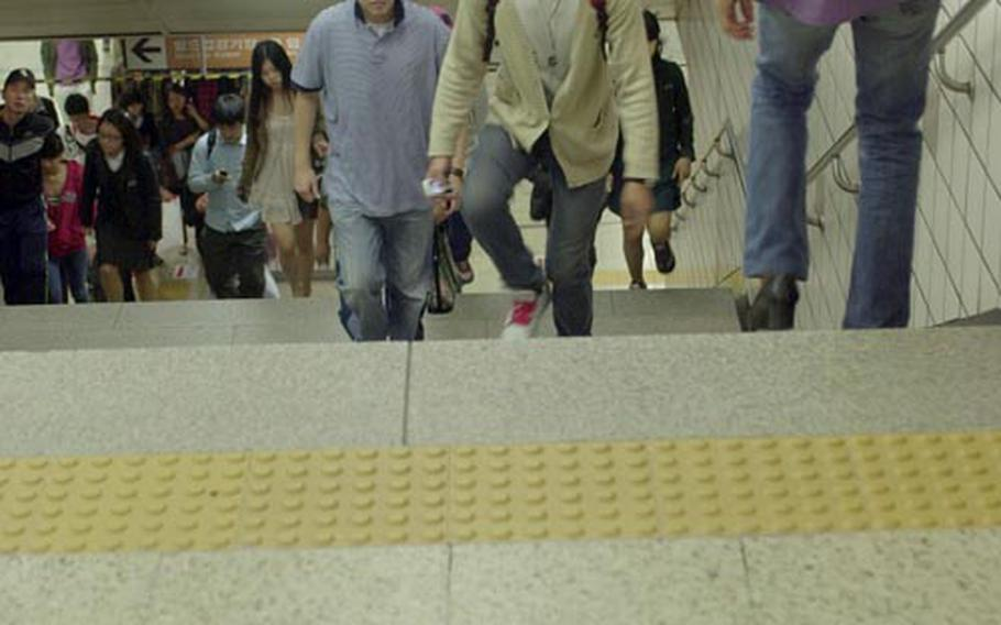 Seoul government officials say it is going to take some time for South Koreans to get in the habit of keeping to the right, as seen at the Itaewon subway station. On Oct. 1, Seoul began a campaign to get everyone to walk on the right. Signs are taped to the floor at the subway station as part of the campaign.