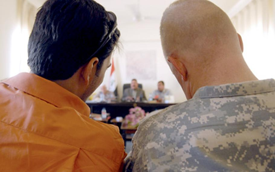 Lt. Col. Eric Timmerman, commander of 1st Battalion, 28th Infantry Regiment, 4th Infantry Brigade Combat Team, sits in the back of the room with an interpreter during a city council meeting in Duluiyah, Iraq, on Tuesday. Not long ago, U.S. troops ran such meetings and struggled to build Iraqi attendance and participation. In Iraq, servicemembers are often both frustrated and relieved by their changing roles from warfighters to peace-builders.