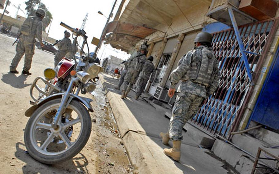 Soldiers with A Company, 1st Battalion, 28th Infantry Regiment patrol down a street in Balad, Iraq after a short meeting with the owners of a U.S.-funded business that gives small loans. U.S. soldiers now rarely patrol unless they are headed to a meeting and spend as little time on the streets as possible.