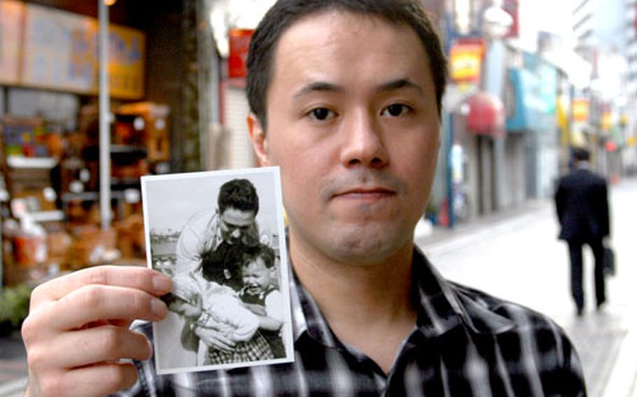 """Masami Nakamura, 33, holds a picture of the grandfather he knows only as """"George"""" holding his young mother and an unidentified child in the late 1940s in Japan. Nakamura is using DNA testing, Web sites and the U.S. government to try to find out more about his grandfather, whom he believes died in the Korean War."""