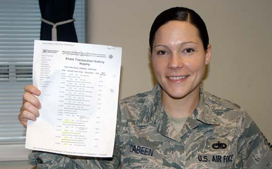 Tech. Sgt. Abbi Cabeen holds a bank statement that lists recent fraudulent charges to her account.