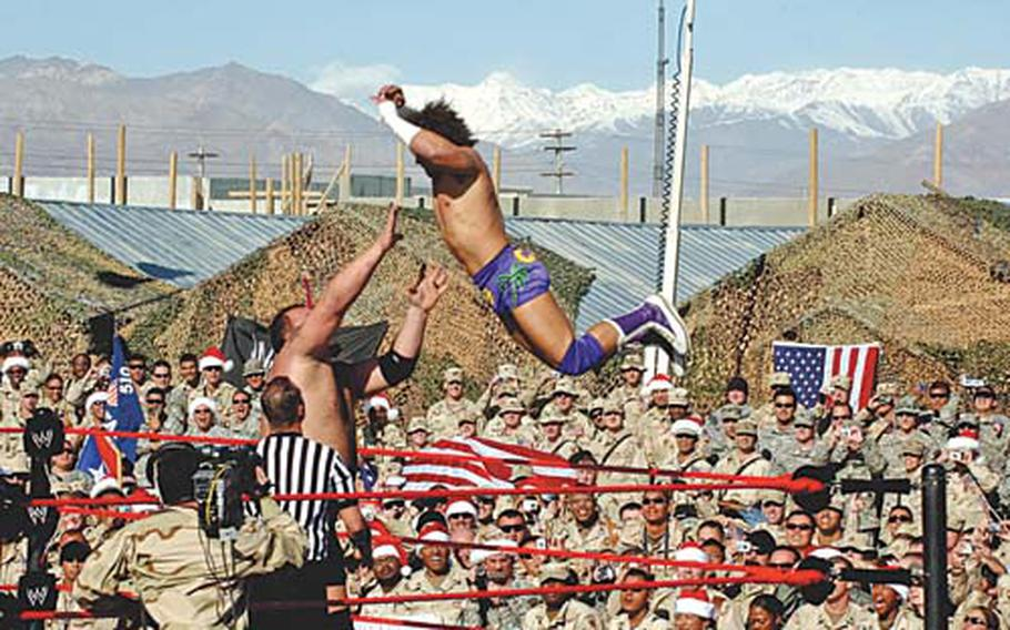 A wrestler with World Wrestling Entertainment throws himself on his partner during a match at Bagram Air Field in 2005. Leisure programs at larger bases will be reviewed with an eye toward focusing more on the mission.