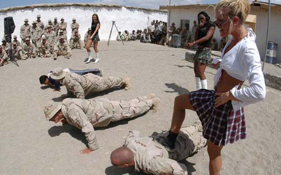 Soldiers do pushups under the watchful eye -- and foot -- of Denver Broncos cheerleader Holly Baack during a July Fourth show at FOB Sweeney in Zabul province in 2005. Leisure programs at larger bases in Afghanistan will be reviewed with an eye toward focusing more on the mission.