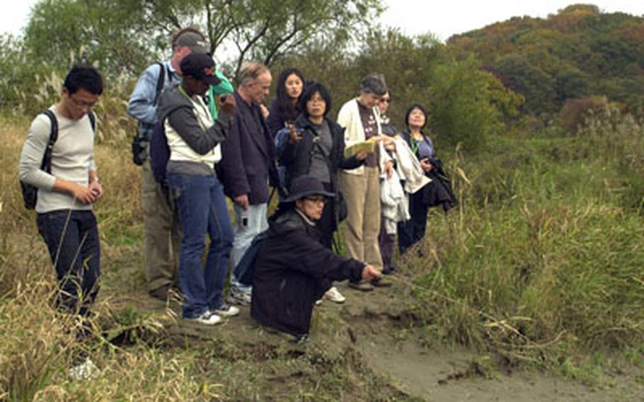 Ecologist Jeon Seon-hee, crouching, talks about animal tracks with visitors during a recent eco-tour she led into the Civilian Control Zone, an area adjacent to Korea's Demilitarized Zone. Jeon is one of many South Koreans already lobbying to keep the DMZ free of development in the event the Koreas someday reunify.