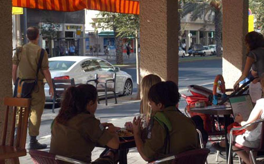 Israeli soldiers grab a bite to eat in Tel Aviv.