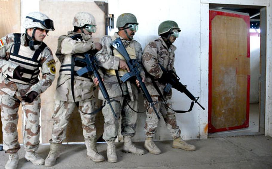 A squad of Iraqi soldiers clears a building during an exercise at the Besmaya Training Center. Housed at a former Republican Guard complex, the center includes 26 weapons ranges, M1A1 tank training and a bomb disposal school. U.S. advisers as a model, but questions remain about the center's future as the U.S. pulls back.