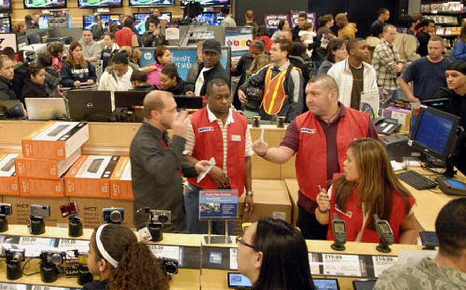 """Power Zone employees work through the bustling """"Black Friday"""" crowd at the Kaiserslautern Military Community Center Base Exchange, Nov. 27, 2009. AAFES holiday sales were up more than 12 percent from last year at Pacific and Europe locations, AAFES offiicials said."""