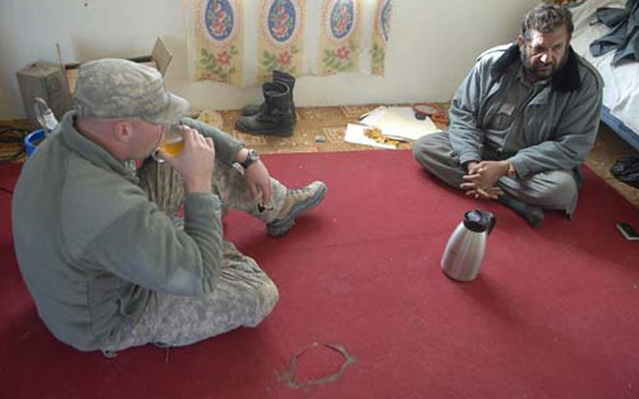 U.S. Army Staff Sgt. Jeff Schaffer drinks tea with an Afghan National Police station commander in Kandahar. Schaffer is part of a platoon moving into the substation as part of a program to train more closely with the Afghan security forces.
