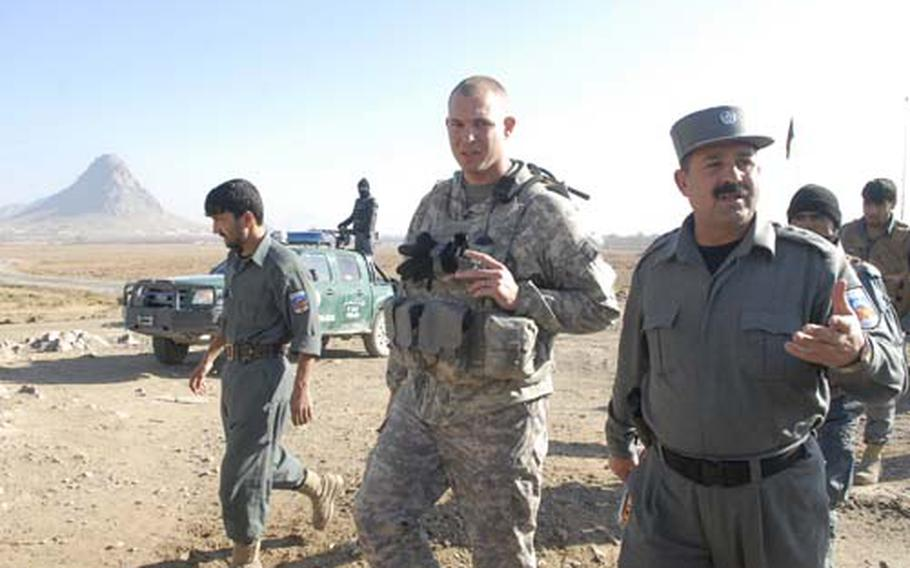 """U.S. Army Capt. Mike Thurman, middle, walks with Kandahar chief of security Col. Fazal """"Shirzad"""" Ahmad on a visit to a checkpoint in the Arghandab Valley near Kandahar city."""