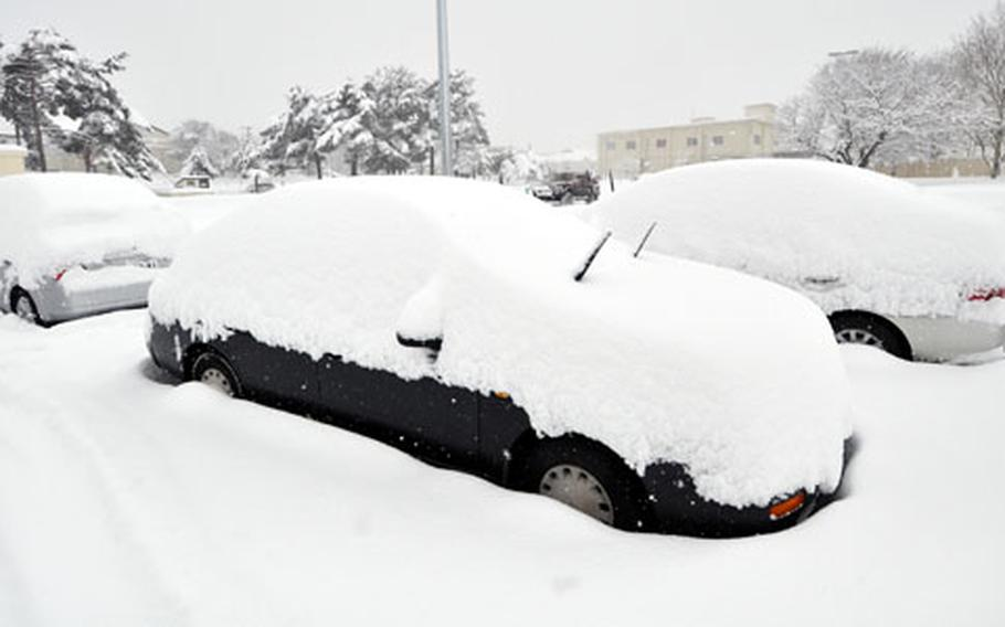 Cars are buried under heavy snow that began Tuesday afternoon and continued to fall through Wednesday morning at Misawa Air Base, Japan.