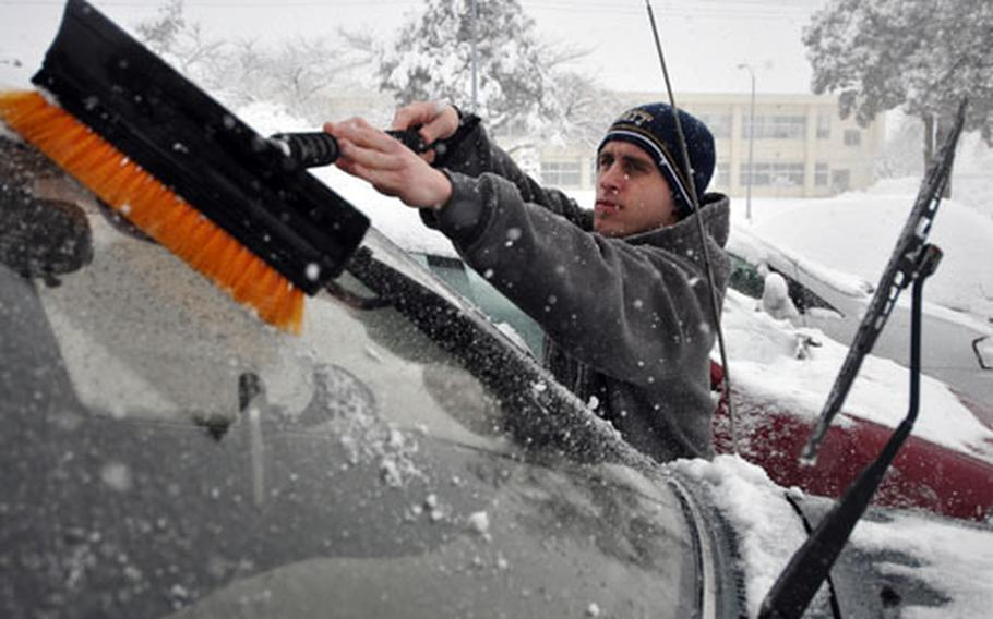 Air Force Staff Sgt. Tim Saar cleans snow of his windshield Wednesday morning at Misawa.