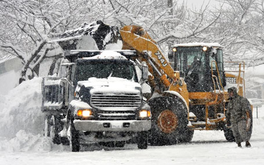 Workers move thousands of pounds of snow into one of a line of dumptrucks in the parking lot of the Army and Air Force Exchange store at Misawa Wednesday morning.
