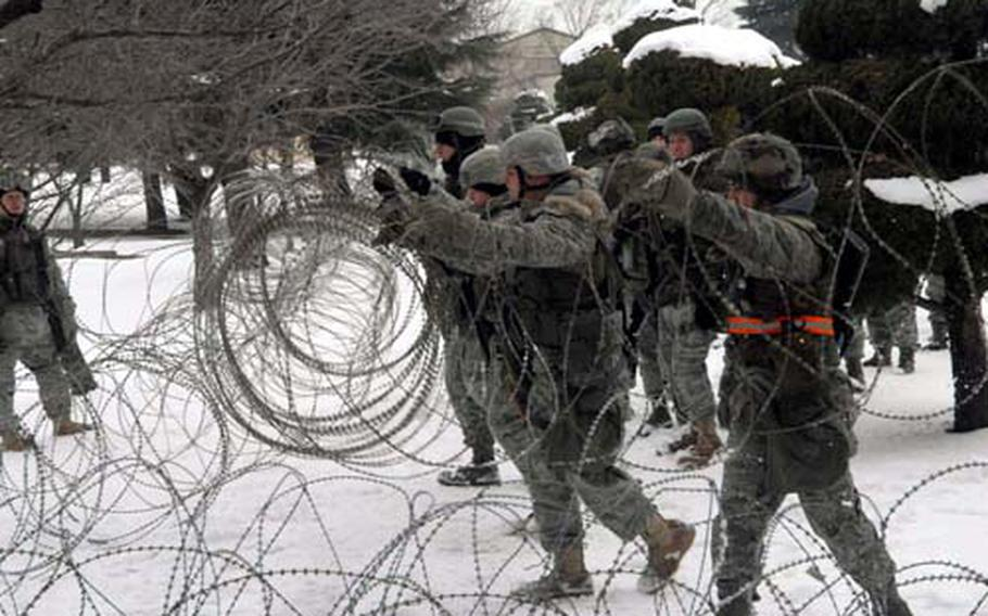 At Kunsan Air Base in South Korea on Monday, airmen of the 8th Fighter Wing set up concertina wire during a mock air war exercise the U.S. 7th Air Force (Air Forces Korea) held across South Korea from Monday to Friday.
