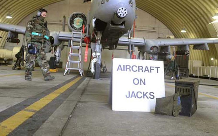 Air Force Staff Sgt. Randal Ogozalek checks the jacks under an A-10 Thunderbolt II attack plane.