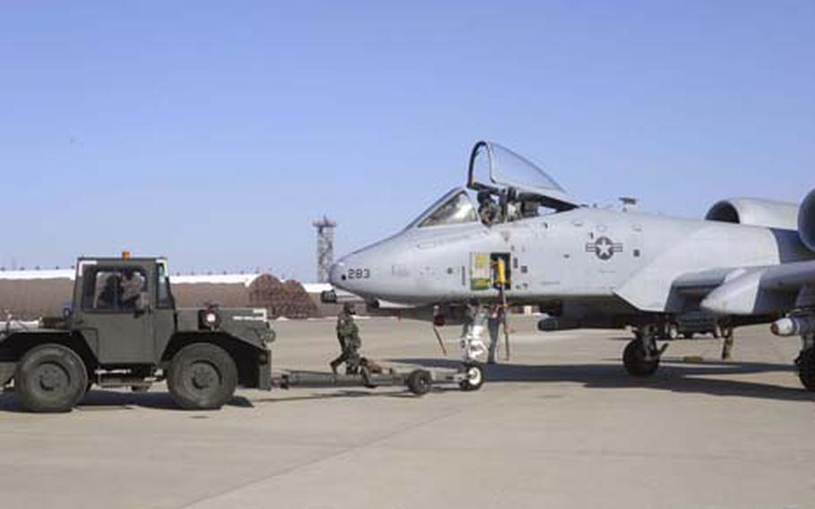 Airmen in chemical protective gear tow an A-10 Thunderbolt II attack plane of the 25th Fighter Squadron to a hangar for maintenance during a mock air war exercise. Some U.S. soldiers and South Korean air force units also took part.