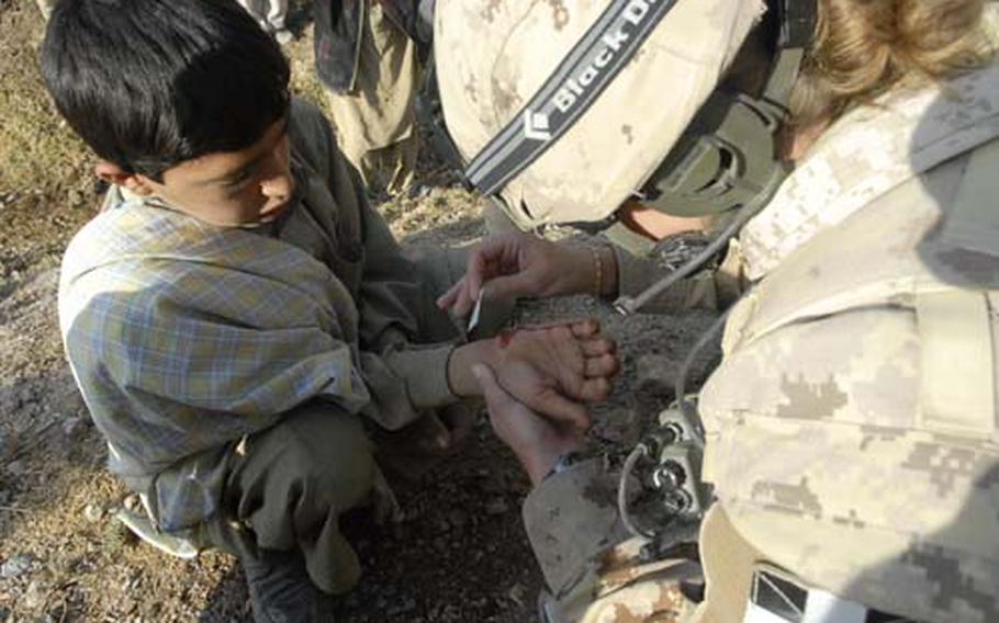 A Canadian medic treats an Afghan boy in Kandahar as part of an effort to develop a better rapport with the residents of the Taliban stronghold.