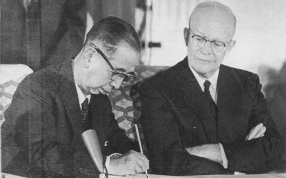 Jan. 19, 1960 Japan Prime Minister Nobusuke Kishi signs the U.S.-Japan military alliance pact on Jan. 19, 1960 with U.S. President Dwight D. Eisenhower looking on. The 50th anniversary of the signing is Tuesday, but the alliance has been strained in recent months over a controversy about basing U.S. Marine aviation units on Okinawa. treaty with President Eisenhpwer looking on.
