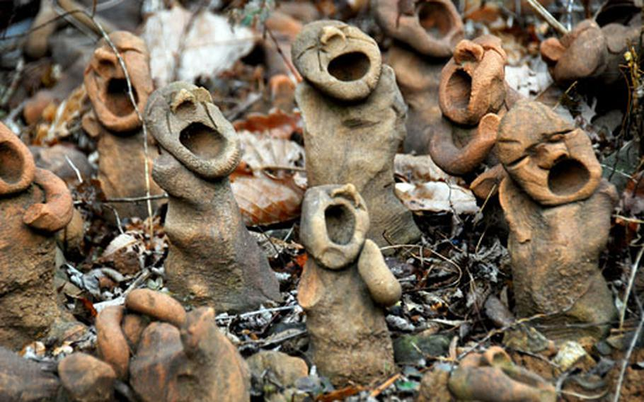 Dozens of small, clay figures are positioned near the entrance to a cave where hundreds of Koreans died during a 1951 U.S. air strike.