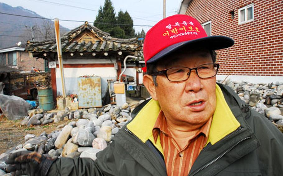 """Um Han-won, 75, stands in front of a small shed that was the only structure to survive a U.S. bombing in 1951. Three hundred and sixty-five people suffocated inside a cave after inhaling napalm from a U.S. bomb. Um, then 16, was one of the cave's 10 survivors. """"I didn't care if I died as long as I could take a breath one last time,"""" said Um, who lost 11 family members, including his mother and six siblings. """"That was the only thing in my head I could think of."""""""