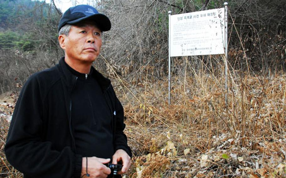 Cho Byung-gyu stands at the edge of a wooded area that is the mass grave for 172 unidentified victims of a 1951 U.S. air raid on a tiny South Korean village. Many among the 360 who died were refugees, and entire families were killed during the attack, making it impossible to identify them. Each grave is marked with a stone and a number assigned to them.