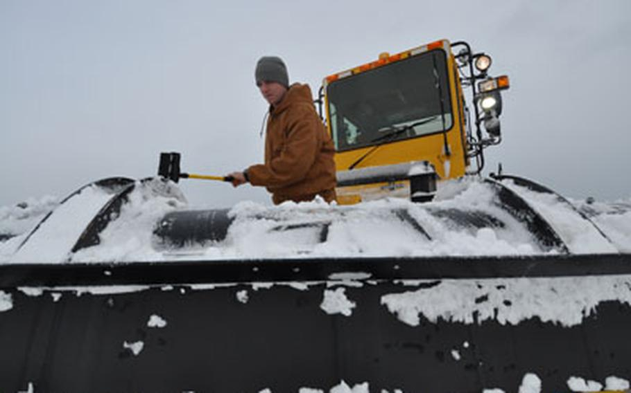 Staff Sgt. Matthew Fenton clears snow of the plow he was using to clear the air field on Wednesday morning following 14 inches of overnight snow at Misawa Air Base, Japan.