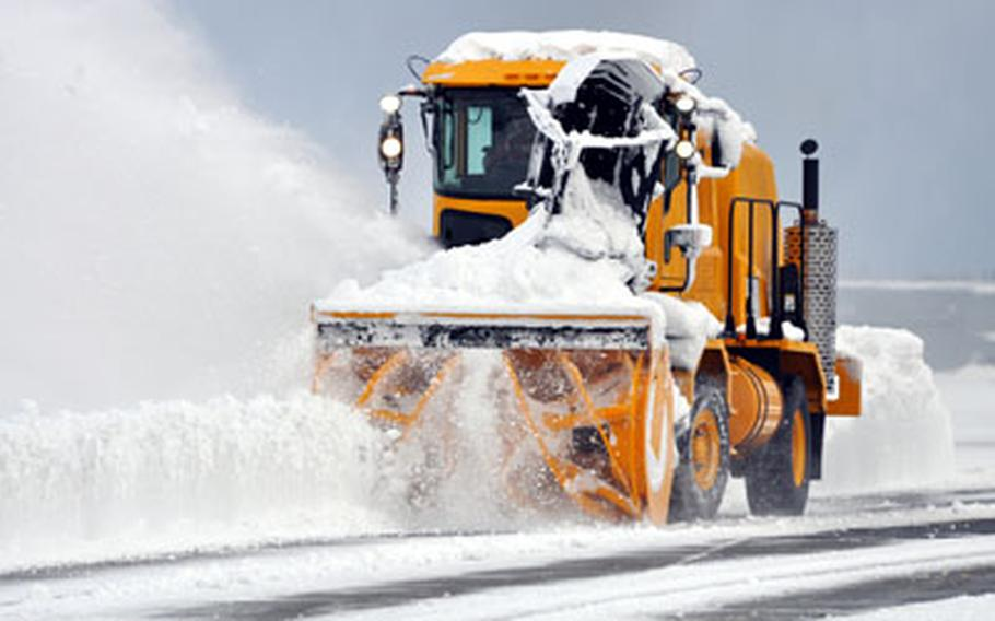 A worker with the 35th Civil Engineer Squadron's heavy repair section plows the air field on Wednesday morning following 14 inches of overnight snow at Misawa Air Base, Japan.