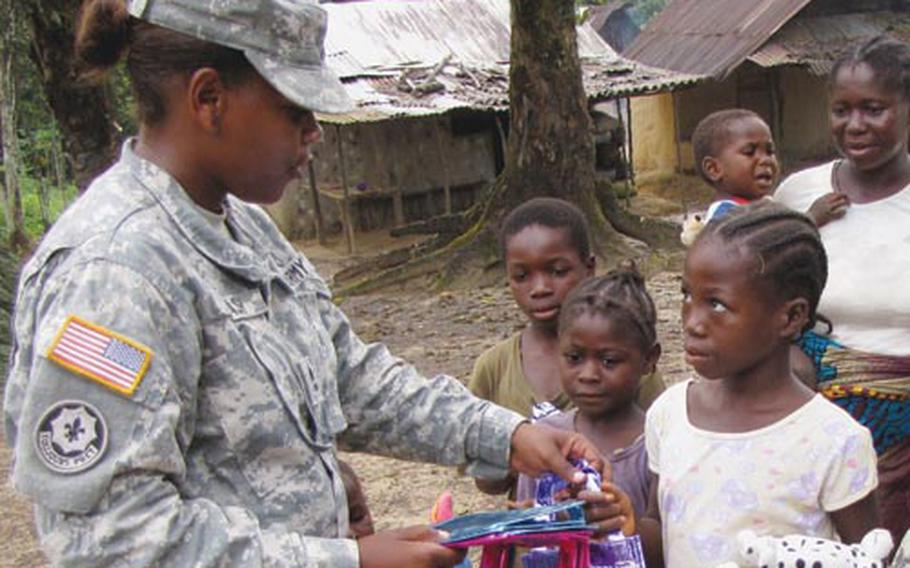 Sgt. 1st Class Dedraf Blash passes out school supplies to children in a Liberian village near Camp Sandi Ware, where she spent three months helping run a military medical clinic and mentoring female soldiers in the Armed Forces of Liberia.