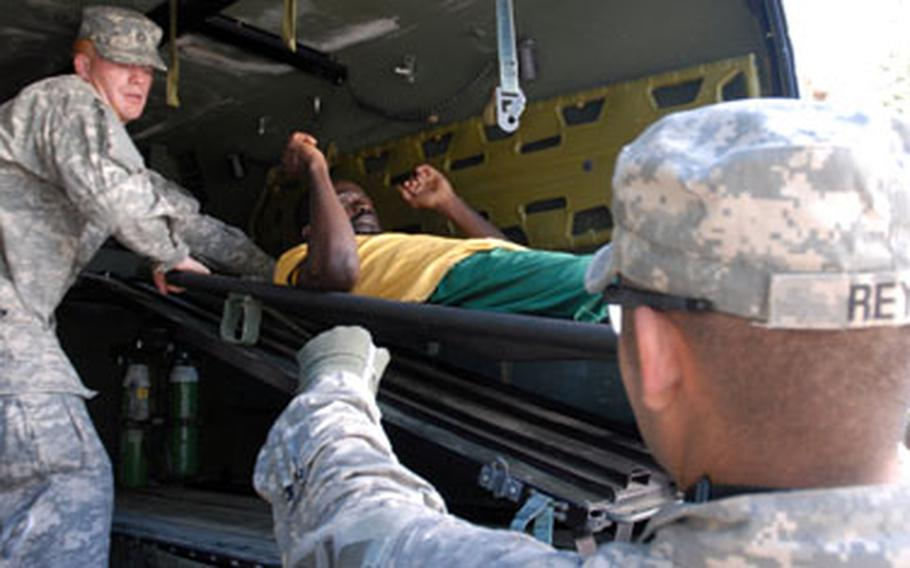 Soldiers unload an injured Haitian man from an Army ambulance Thursday to evacuate him to the USNS Comfort.