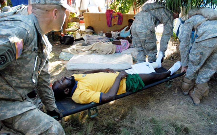 Soldiers carry an injured Haitian man from the main Port-au-Prince hospital to an Army ambulance, which was taking patients to the presidential palace for a helicopter transport to the USNS Comfort on Thursday.
