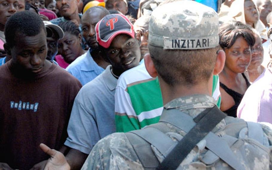 Pfc. Anthony Inzitari stands at the gate Friday talking to Haitians who were trying to get inside the main Port-au-Prince hospital.