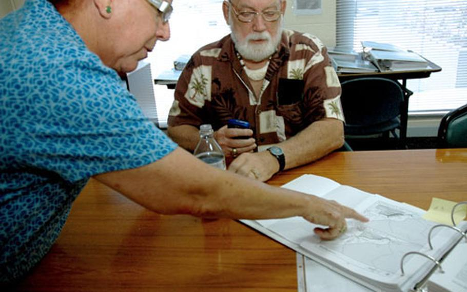 Guam Sen. Judith Guthertz, who chairs the legislative committee on the buildup, looks at part of the military's proposal with her chief of staff, retired Navy captain Richard Wyttenbach-Santos. Guthertz has requested the military take another look at its own land – including the 15,000 acres it has at Andersen Air Force Base – before asking to buy or lease Guam-controlled land.