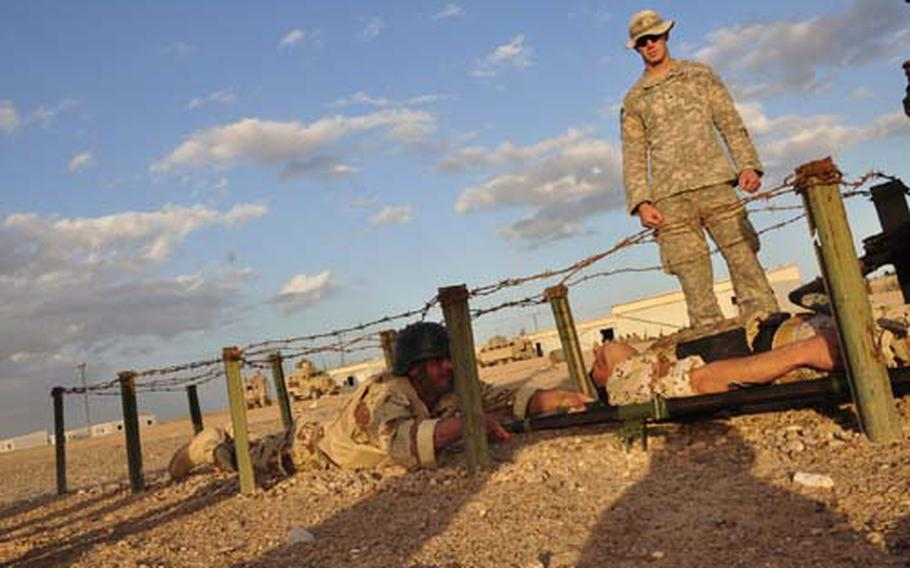 Sgt. William Winstead watches Iraqi soldiers crawl under barbed wire while hauling a soldier playing an injury victim on a litter. The Iraqi soldiers were participating in a timed obstacle course as part of their training in combat first aid.