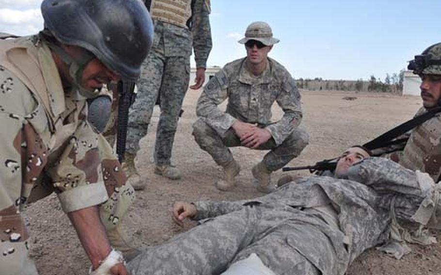 Sgt. William Winstead watches as soldiers with Iraq's 1st Army Division practice stanching wounds with bandages applying tourniquets during a combat first aid class.