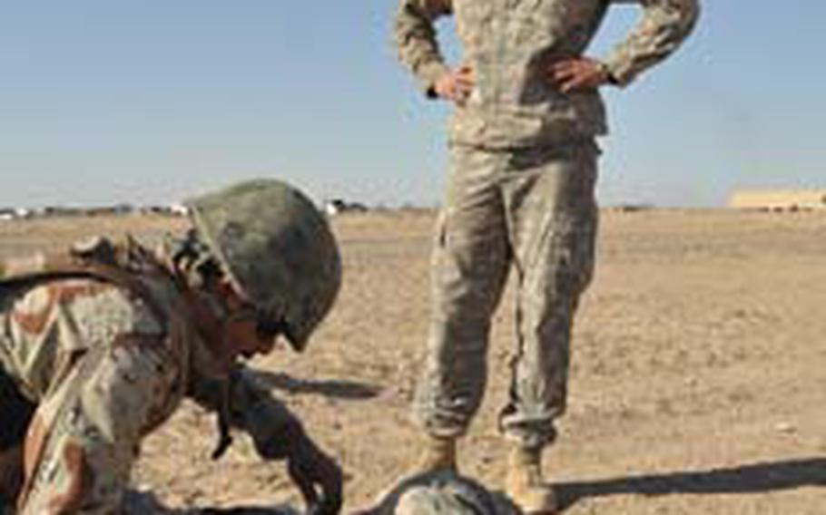 Iraqi soldier Metaer Bazier treats Spc. Damon Ferguson for injuries, while Sgt. Carl Moore looks on.