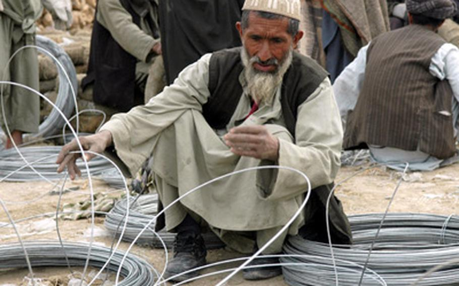 A local worker in Nawa bends wires into cylinders, which will be used as farming tunnels.