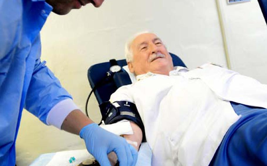 Petty Officer 3rd Class Jason Schrunk prepares to complete the blood drawing process as 76-year-old retired Air Force Staff Sgt. Dennis Provencher donates his 34th recorded gallon of blood Thursday at the American Red Cross Center on Camp Foster. Provencher has been regularly donating blood since arriving on Okinawa in 1961 and is currently recognized by the Guinness Book of World Records as donating more blood than anybody else.
