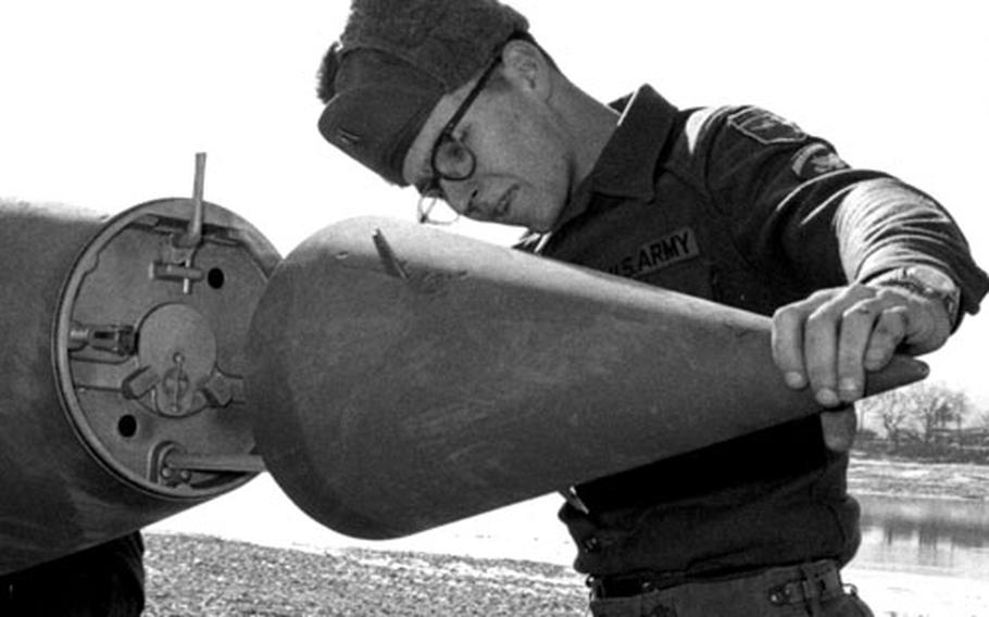 Spc. 5 Levi A. Bragdon, a senior assembly specialist, prepares the nose cone of an Honest John missile for launch in South Korea in January, 1969.
