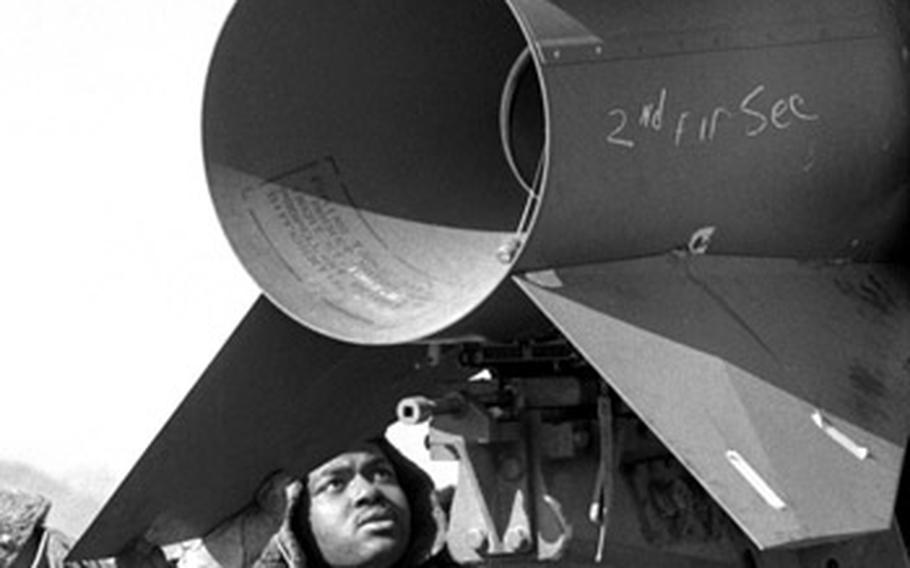 Crewmen from 1st Battalion, 42nd Artillery, check out the fittings on an Honest John missile's tail fins.