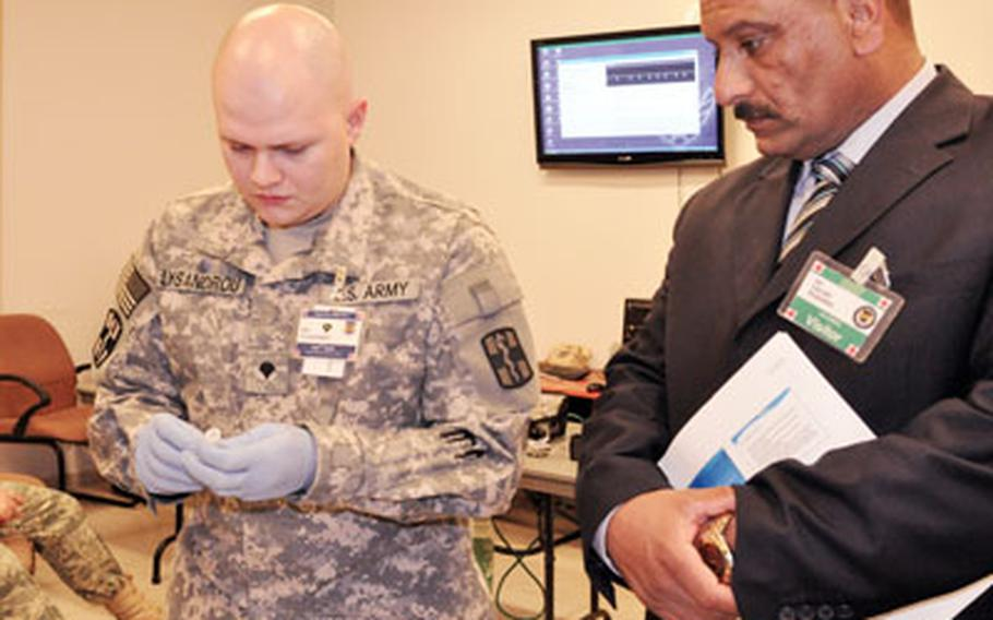 Spc. James Lysandrou, of the 932nd Blood Support Detachment, shows a rapid test for HIV and Hepatitis B and C to Faez Farhan Muhammad, director of the Ibn Firnas clinic in Albu Hassan. Staff from Muhammad's clinic will soon learn with their American peers at a new medical training facility just outside the gates of Balad.