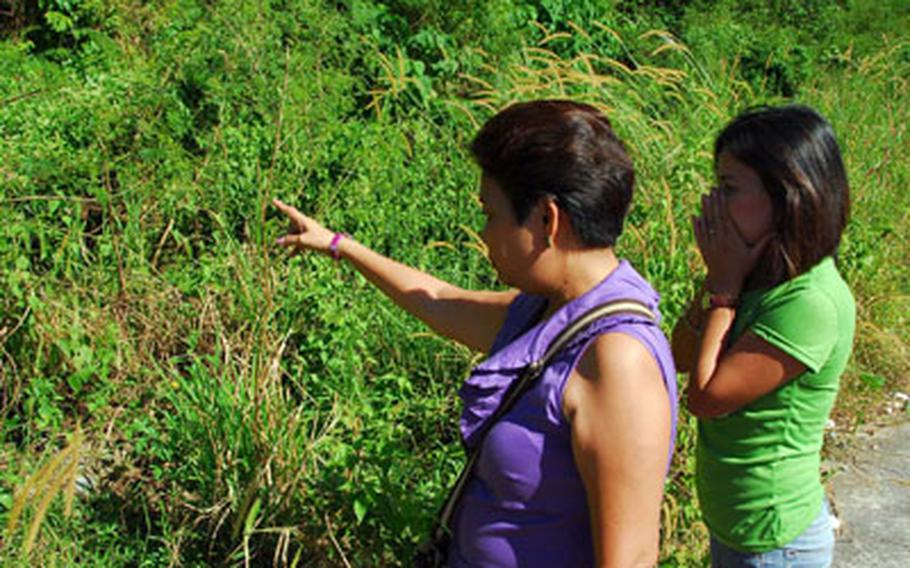 Ruby Ramores (center) in November shows Lilibeth Eniceo the spot along a rural road where her brother was shot to death and left. Eniceo says she hired the gunman who did the shooting.