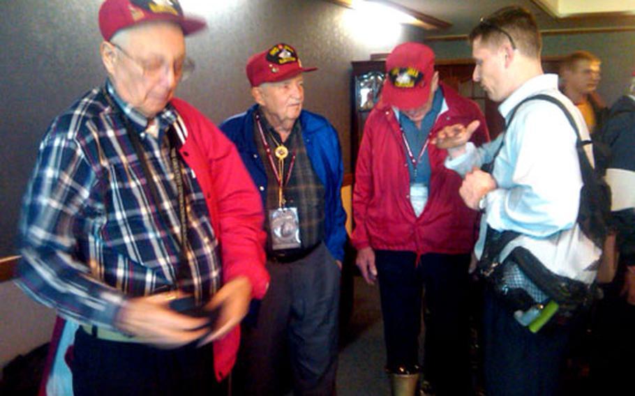 World War II veterans wait at Kadena Air Base for their flight to Iwo Jima.