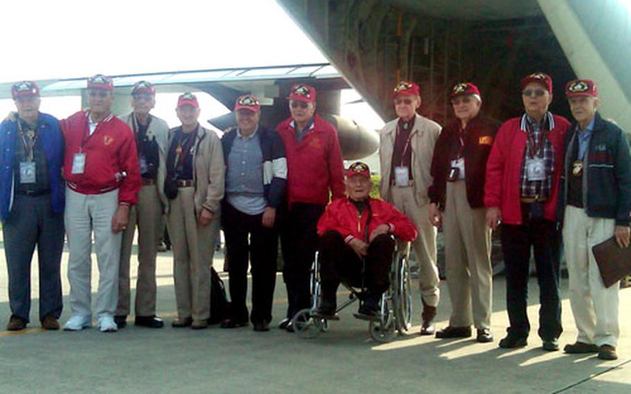 The veterans pose for a photo in front of the plane they were hoping would be their ride to Iwo Jima.