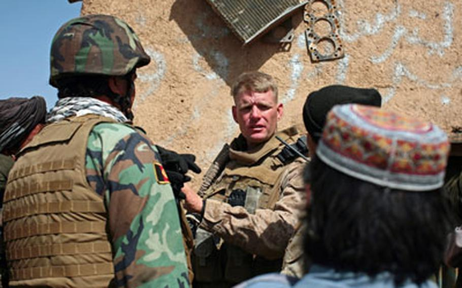 Lt. Col. Brian Christmas, commander of 3rd Battalion, 6th Marine Regiment, listens to the concerns of a local villager through a translator in the village of Marjah, Afghanistan.