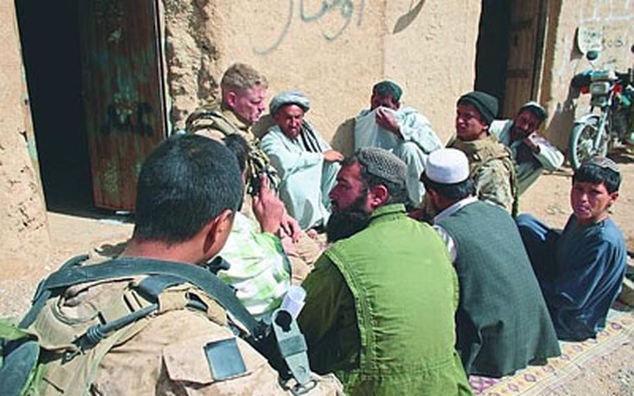 Lt. Col. Brian Christmas, commander of 3rd Battalion, 6th Marine Regiment, meets Friday with men in Marjah, Afghanistan, to discuss reopening a school there. Villagers want a new school but fear the Taliban will punish them for cooperating with U.S. forces.