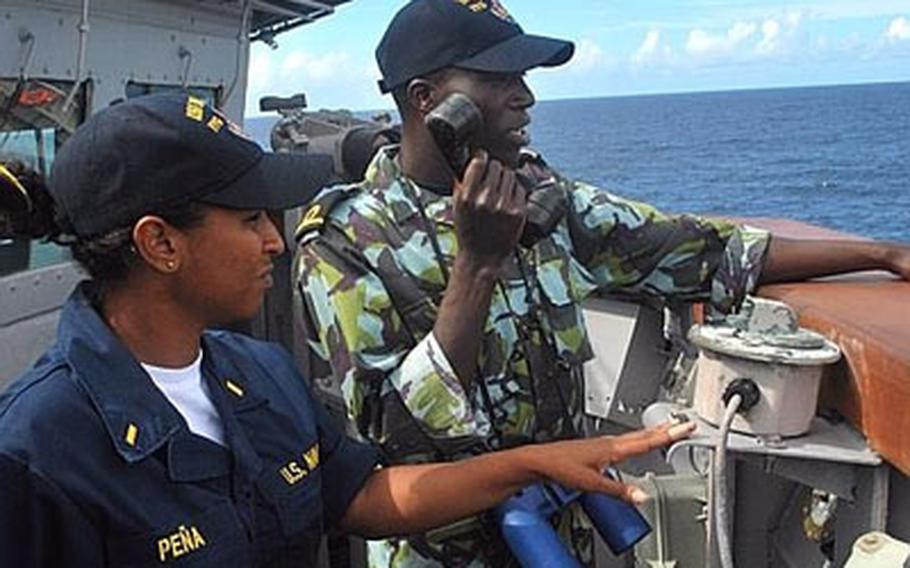 Ensign Emily Pena, left, an engineering officer aboard the guided-missile frigate USS Nicholas, instructs an Africa Partnership Station East student how to communicate ship coordinates with the bridge during a man-overboard drill.