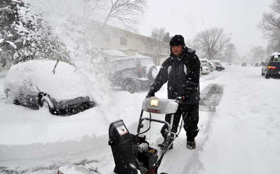 Air Force Master Sgt. Greg Pocaigue uses a snowblower to dig out his car.