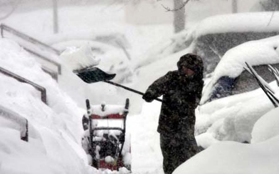 A housing area resident digs out his sidewalk Wednesday during a blizzard that hit Misawa Air Base, Japan.